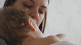Μητέρα και αυτή λίγο αγοράκι στο κρεβάτι στο ηλιόλουστο δωμάτιο απόθεμα βίντεο