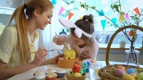 Μητέρα και αυτή λίγη κόρη με τα αυτιά λαγουδάκι που χρωματίζει το λαγουδάκι Πάσχας φιλμ μικρού μήκους