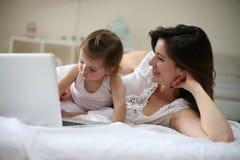 Μητέρα και αυτή λίγο μωρό στο σπίτι Μητέρα με το μωρό της που χρησιμοποιεί το λ Στοκ Φωτογραφίες