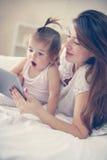 Μητέρα και αυτή λίγο μωρό στο σπίτι Μητέρα με το μωρό της που χρησιμοποιεί το τ Στοκ Εικόνες