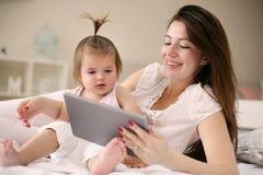 Μητέρα και αυτή λίγο μωρό στο σπίτι Μητέρα με το μωρό της watchin Στοκ Εικόνες