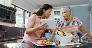 Μητέρα και γιαγιά που βοηθούν το κορίτσι για να αναμίξει τη σαλάτα 4K 4k απόθεμα βίντεο