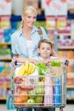 Μητέρα και γιος με το σύνολο κάρρων των προϊόντων στη λεωφόρο αγορών Στοκ φωτογραφίες με δικαίωμα ελεύθερης χρήσης