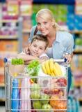 Μητέρα και γιος με το σύνολο κάρρων των προϊόντων στο κατάστημα Στοκ Εικόνες