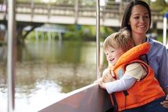 Μητέρα και γιος που απολαμβάνουν την ημέρα έξω στη βάρκα στον ποταμό από κοινού Στοκ Φωτογραφία