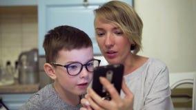 Μητέρα και γιος που εξετάζουν καταπληκτικά την οθόνη smartphone απόθεμα βίντεο