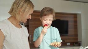 Μητέρα και γιος που τρώνε τις φράουλες στην κουζίνα Ευτυχής οικογενειακή έννοια απόθεμα βίντεο