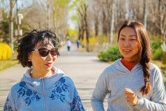 Μητέρα και ενήλικη κόρη που τρέχουν για τον αθλητισμό στο πάρκο για την καλύτερη ικανότητα στοκ φωτογραφία