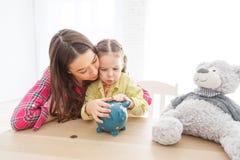 Μητέρα και η κόρη παιδιών της που βάζουν το νόμισμα στη piggy τράπεζα στοκ εικόνα