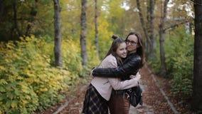 Μητέρα και κόρη ένας έφηβος που περπατά, που μιλά και που αγκαλιάζει στο πάρκο φθινοπώρου απόθεμα βίντεο