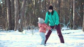 Μητέρα και κόρη κοριτσάκι που παίζουν και που γελούν το χειμώνα υπαίθρια στο χιόνι φιλμ μικρού μήκους