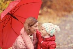 Μητέρα και κόρη με την ομπρέλα στο πάρκο φθινοπώρου στοκ φωτογραφία με δικαίωμα ελεύθερης χρήσης