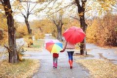 Μητέρα και κόρη με τις ομπρέλες που παίρνουν τον περίπατο στο πάρκο φθινοπώρου στοκ εικόνα με δικαίωμα ελεύθερης χρήσης