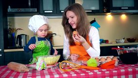 Μητέρα και κόρη με το αυγό μαγειρεύοντας το κέικ μαζί στην κουζίνα απόθεμα βίντεο