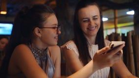 Μητέρα και κόρη με το ενδιαφέρον και την ευχαρίστηση που εξετάζουν τις φωτογραφίες στο έξυπνο τηλέφωνο, που κάθεται σε έναν πίνακ απόθεμα βίντεο