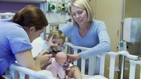 Μητέρα και κόρη με το προσωπικό στον παιδιατρικό θάλαμο του νοσοκομείου απόθεμα βίντεο