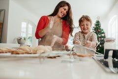 Μητέρα και κόρη που έχουν τη διασκέδαση κατασκευάζοντας τα μπισκότα Χριστουγέννων Στοκ εικόνες με δικαίωμα ελεύθερης χρήσης