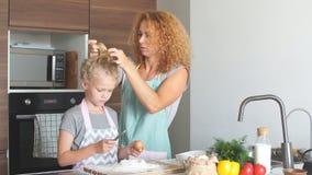 Μητέρα και κόρη που έχουν τη διασκέδαση στην κουζίνα προετοιμάζοντας τα μπισκότα φιλμ μικρού μήκους