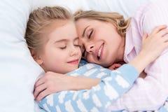 μητέρα και κόρη που αγκαλιάζουν και που κοιμούνται στο κρεβάτι Στοκ φωτογραφίες με δικαίωμα ελεύθερης χρήσης