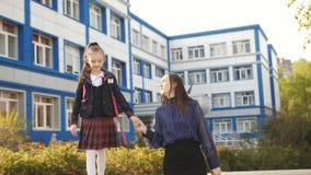 Μητέρα και κόρη που αγκαλιάζουν κοντά στο σχολείο μετά από το σχολείο Μια μητέρα με μια νέα κόρη στη σχολική στολή δίπλα φιλμ μικρού μήκους