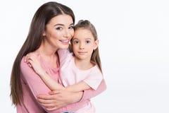 Μητέρα και κόρη που αγκαλιάζουν και που χαμογελούν στη κάμερα στο λευκό στοκ φωτογραφία