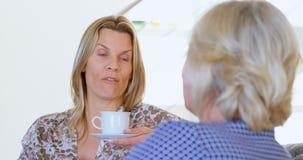 Μητέρα και κόρη που αλληλεπιδρούν η μια με την άλλη ενώ έχοντας τον καφέ 4k απόθεμα βίντεο