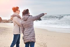 Μητέρα και κόρη που απολαμβάνουν το ηλιοβασίλεμα στην παραλία Στοκ Φωτογραφία