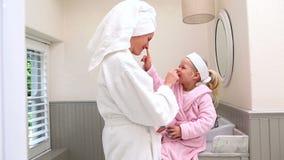 Μητέρα και κόρη που βάζουν την κρέμα προσώπου επάνω απόθεμα βίντεο