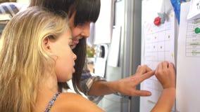 Μητέρα και κόρη που βάζουν το αστέρι στο διάγραμμα ανταμοιβής απόθεμα βίντεο