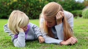 Μητέρα και κόρη που βρίσκονται στην ομιλία χλόης απόθεμα βίντεο