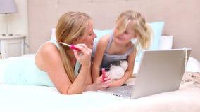 Μητέρα και κόρη που βρίσκονται στο κρεβάτι που χρησιμοποιεί το lap-top φιλμ μικρού μήκους
