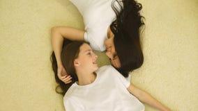Μητέρα και κόρη που βρίσκονται στο κρεβάτι στις ρόδινες πυτζάμες, χαμογελώντας μητέρα, κόρη που γελά, τοπ άποψη φιλμ μικρού μήκους