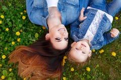 Μητέρα και κόρη που βρίσκονται στο χορτοτάπητα Στοκ φωτογραφία με δικαίωμα ελεύθερης χρήσης