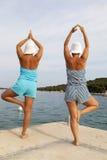 Μητέρα και κόρη που εκτελούν το joga στην ηλιόλουστη παραλία Στοκ Φωτογραφία