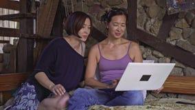 Μητέρα και κόρη που εξετάζουν τις φωτογραφίες στο lap-top στο σπίτι απόθεμα βίντεο
