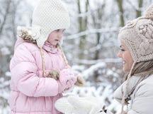 Μητέρα και κόρη που διαμορφώνουν τη χιονιά το χειμώνα Στοκ Εικόνες