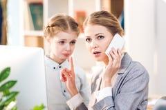 Μητέρα και κόρη που μιλούν στο επιχειρησιακό γραφείο, επιχειρηματίας που χρησιμοποιεί το smartphone Στοκ Φωτογραφίες