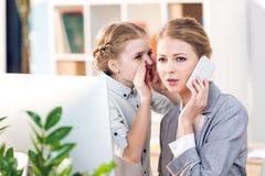 Μητέρα και κόρη που μιλούν στο επιχειρησιακό γραφείο, επιχειρηματίας που χρησιμοποιεί το smartphone Στοκ Φωτογραφία