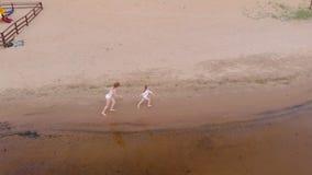 Μητέρα και κόρη που οργανώνονται κατά μήκος του ποταμού κατά μήκος της άμμου E Ηλιόλουστη θερινή ημέρα Εναέριος βλαστός φιλμ μικρού μήκους