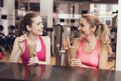 Μητέρα και κόρη που πίνουν τα πρωτεϊνικά κουνήματα στη γυμναστική Φαίνονται ευτυχείς, μοντέρνοι και κατάλληλοι Στοκ φωτογραφία με δικαίωμα ελεύθερης χρήσης