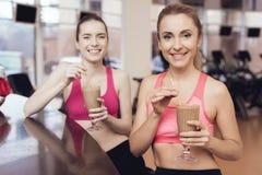 Μητέρα και κόρη που πίνουν τα πρωτεϊνικά κουνήματα στη γυμναστική Φαίνονται ευτυχείς, μοντέρνοι και κατάλληλοι Στοκ Εικόνες