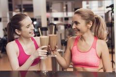 Μητέρα και κόρη που πίνουν τα πρωτεϊνικά κουνήματα στη γυμναστική Φαίνονται ευτυχείς, μοντέρνοι και κατάλληλοι Στοκ εικόνα με δικαίωμα ελεύθερης χρήσης