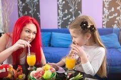 Μητέρα και κόρη που πίνουν το χυμό από πορτοκάλι Στοκ φωτογραφία με δικαίωμα ελεύθερης χρήσης