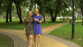 Μητέρα και κόρη που περπατούν κατά μήκος του πάρκου που κουβεντιάζει και που γελά, χόμπι από κοινού απόθεμα βίντεο