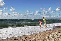Μητέρα και κόρη που περπατούν στην ακτή της θάλασσας της Βαλτικής στοκ εικόνα
