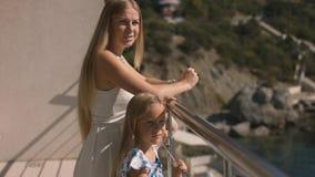 Μητέρα και κόρη που στέκονται σε ένα ανοικτό μπαλκόνι που αγνοεί τη θάλασσα Στοκ Εικόνα