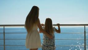 Μητέρα και κόρη που στέκονται στο υπαίθριο πεζούλι που αγνοεί τη θάλασσα Στοκ φωτογραφία με δικαίωμα ελεύθερης χρήσης