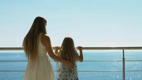 Μητέρα και κόρη που στέκονται στο υπαίθριο πεζούλι που αγνοεί τη θάλασσα Στοκ Φωτογραφία