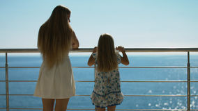 Μητέρα και κόρη που στέκονται στο υπαίθριο πεζούλι που αγνοεί τη θάλασσα Στοκ Εικόνες