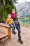 Μητέρα και κόρη που στηρίζονται στον ξύλινο πίνακα πικ-νίκ στη λίμνη Bries στοκ εικόνες